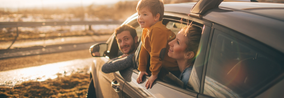 Man, woman, and Child leaning out the window of a car
