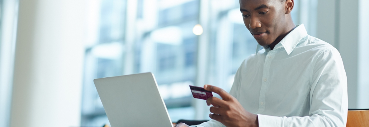 Man with computer using credit card