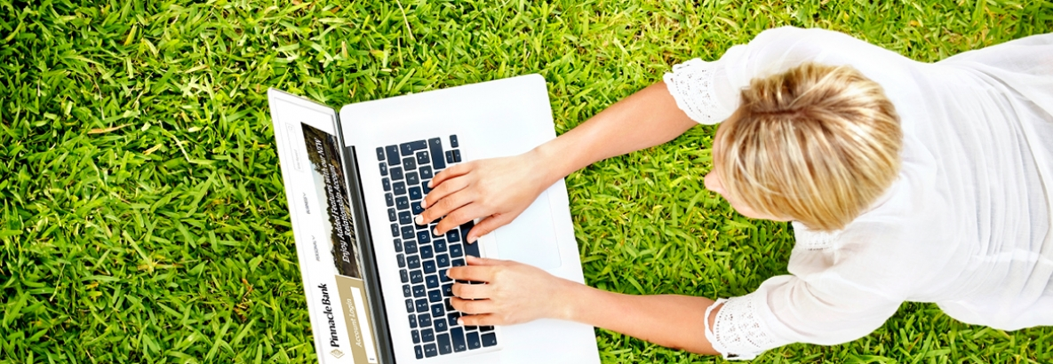 person laying in the grass using a lap top