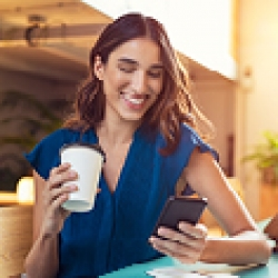 Picture of a woman drinking coffee looking at her phone